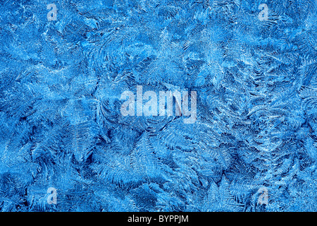 Frost patterns on window glass in winter - Stock Photo