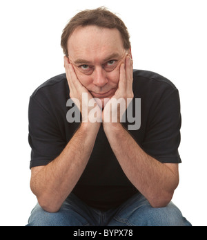 adult man sat with his head in his hands glancing upwards, he is casually dressed and isolated against a white background - Stock Photo