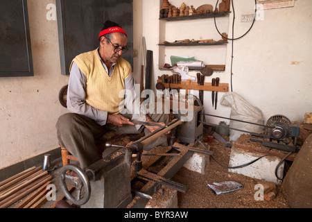 India, Rajasthan, Udaipur, wood turner using lathe in old city - Stock Photo