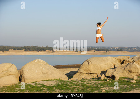 A Woman Jumping for Joy on some rocks - Stock Photo
