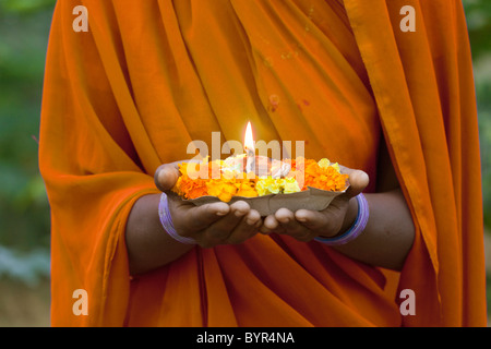 India, Uttar Pradesh, close up of woman's hands holding prayer candle with marigold flowers - Stock Photo