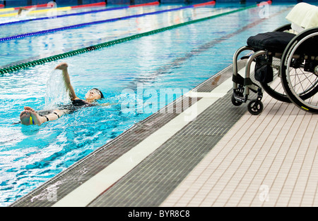 a paraplegic woman swims in a pool with her wheelchair at the edge of the pool; edmonton, alberta, canada - Stock Photo