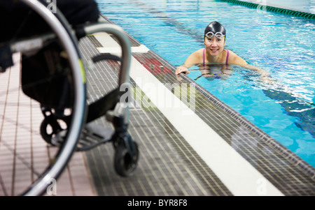 a paraplegic woman swims in a pool with her wheelchair at the water's edge; edmonton, alberta, canada - Stock Photo