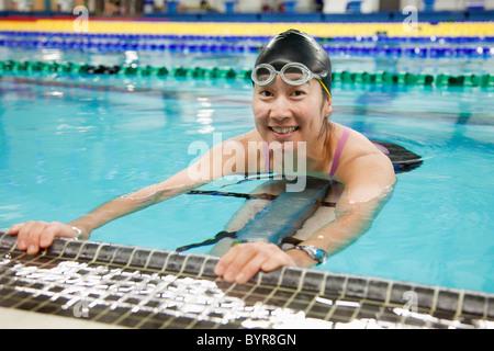 a paraplegic woman swims in a pool; edmonton, alberta, canada - Stock Photo