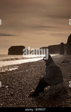 a man wearing a coat and hood sitting on a rock by the shore; south shields, tyne and wear, england - Stock Photo