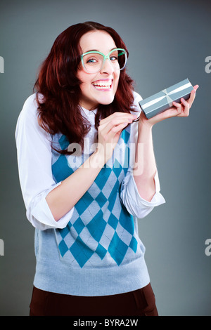Geeky woman ecstatic with gift box - Stock Photo