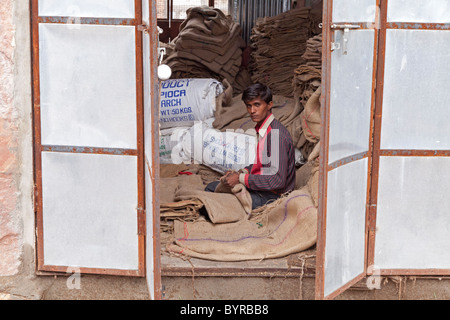 India, Rajasthan, jodhpur young man repairing hessian sacks framed by metal shutters - Stock Photo
