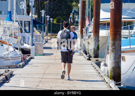 a father holding his young son as he walks down a pier in a marina; victoria, british columbia, canada - Stock Photo