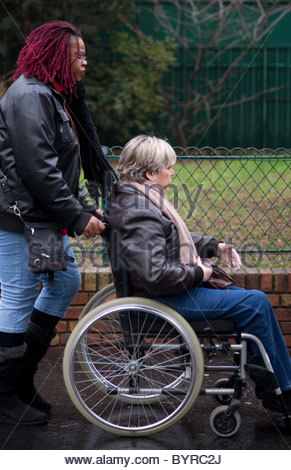 Disabled person in wheelchair being pushed along a street by a friend - person Paris France - Stock Photo