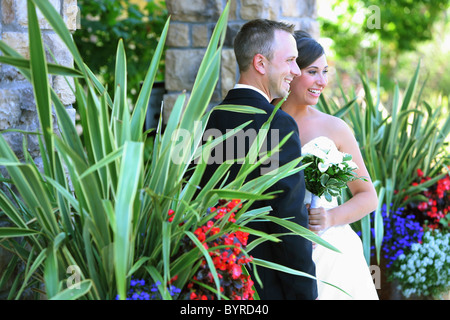 a bride and groom posing for pictures in a garden area; troutdale, oregon, united states of america - Stock Photo