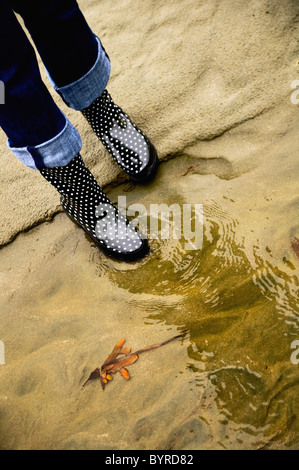 a woman's rain boots reflected in the water; seattle, washington, united states of america - Stock Photo