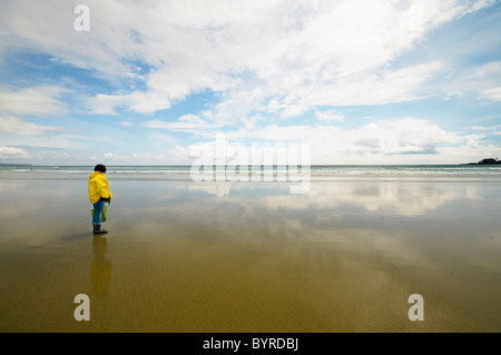 a woman in a raincoat looking out at the ocean while standing on the beach; tofino, british columbia, canada - Stock Photo