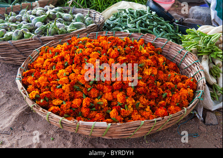 Basket of Marigold flowers for making garlands at an Indian street vegetable market. Andhra Pradesh, India - Stock Photo