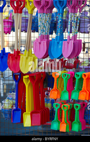 A colourful array of plastic buckets and spades for children to play with on the beach. - Stock Photo