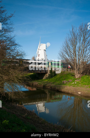 Southern Train Passing Over The River Tillingham by Rye Windmill East Sussex England - Stock Photo