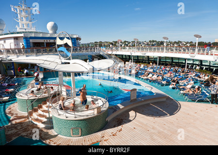 Senior men and women sit in hot tub and on lounge chairs on the deck of Royal Caribbean's Jewel of the Seas cruise - Stock Photo