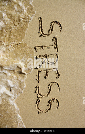 'Stress' written out in wet sand, being washed away by the sea. Please see my collection for more similar photos. - Stock Photo