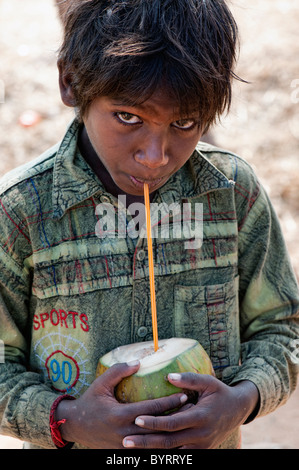 Happy young poor lower caste Indian street boy drinking coconut water. Andhra Pradesh, India - Stock Photo