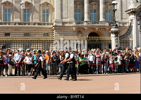 Crowds and Police outside Buckingham Palace waiting for Changing the Guard - Stock Photo