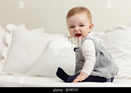portrait of 6 months female child playing on bed and smiling at camera. Horizontal shape, side view, full length, - Stock Photo