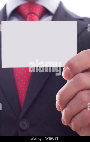 Businessman in grey suit and a blue shirt with a red power tie, shows businesscard with copy space, shallow dept - Stock Photo