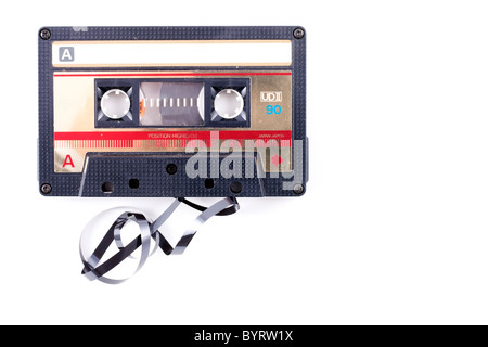 vintage cassette, black with red and gold, some of the tape is coming out of the cassette isolated on white with - Stock Photo