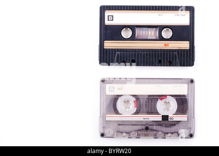 two vintage cassette tapes in black and transparent isolated on white and with copy space - Stock Photo