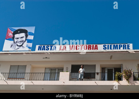 Man on a balcony and a Cuban propaganda sign with the picture of Che an Cuban flag. Camaguey, Cuba, Caribbean. - Stock Photo