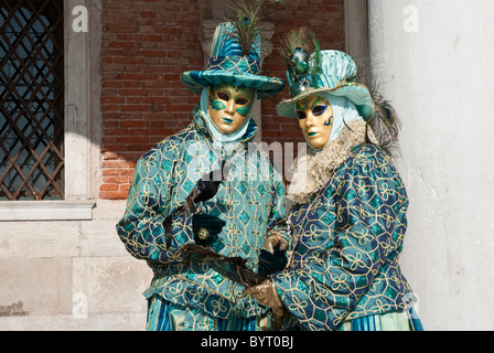 A couple of venetian masks during Carnival handling bird and peacock plumes. Posing  under a portico near a column - Stock Photo