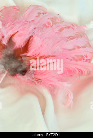 Pink feather hand held fan on silk - Stock Photo