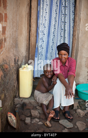 A young urban HIV positive mother and child sit outside their house in Kampala, Uganda, East Africa. - Stock Photo
