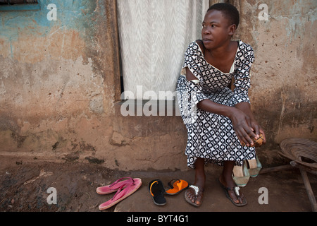 A young urban woman sits outside on her doorstep in Kampala, Uganda, East Africa. - Stock Photo