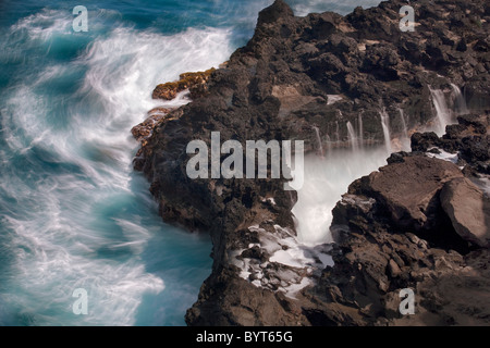 Rough surf off rocky Maui, Hawaii coastline. - Stock Photo