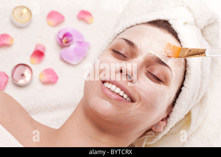 Applying of soothing mask, young woman getting spa procedures. - Stock Photo