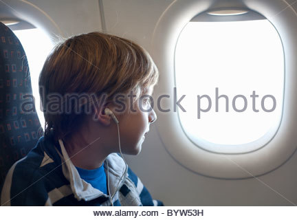 Boy on airplane looking out of window - Stock Photo