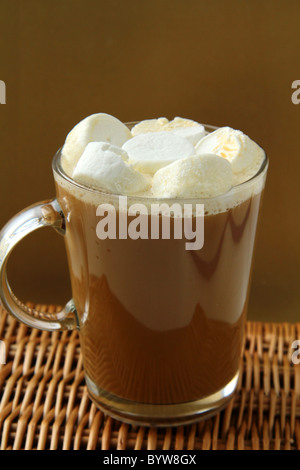 Coffee with marshmallows in large glass beaker on a gold background - Stock Photo