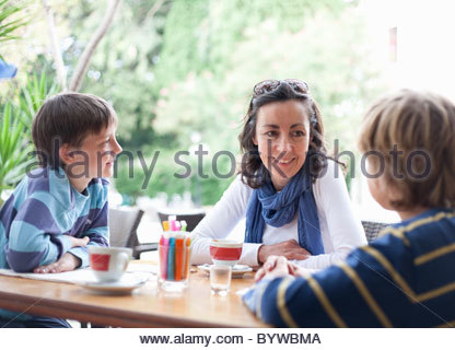 Woman at cafe with two boys - Stock Photo