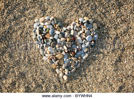 Heart made of pebbles on beach - Stock Photo