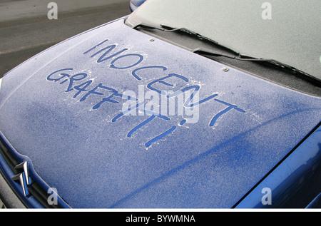 innocent grafitti on car bonnet - Stock Photo