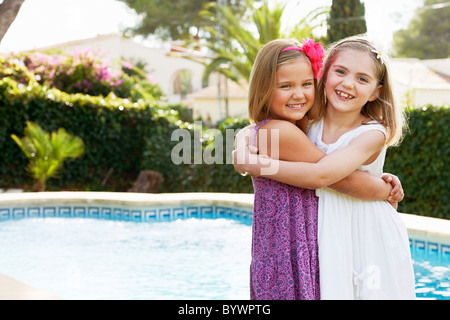 Girls hugging each other by pool - Stock Photo
