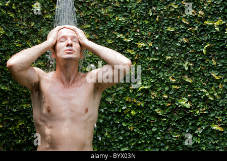 Man taking a shower outside - Stock Photo