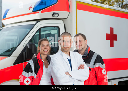 Doctor and paramedics in front of coach - Stock Photo