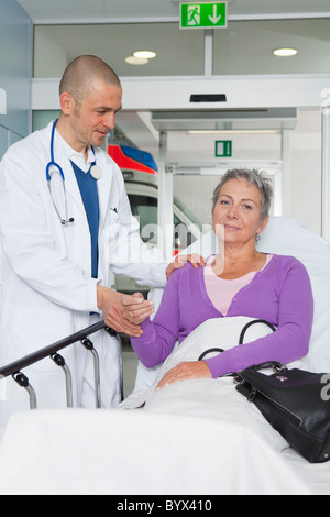 Doctor taking womans pulse - Stock Photo