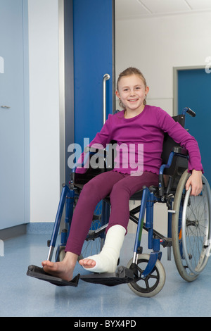 Girl in wheelchair, foot in plaster - Stock Photo