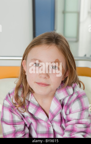 Girl with plaster in hospital bed - Stock Photo