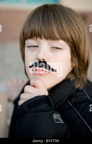 An eight year old boy wearing a pretend moustache with hand on chin, acting like an adult man in deep thought. - Stock Photo