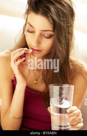 Girl taking tablet - Stock Photo