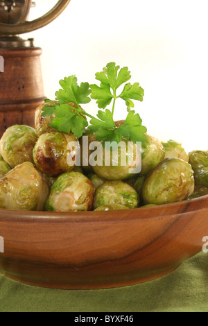 roasted brussels sprouts in a wooden bowl on a green napkin - Stock Photo