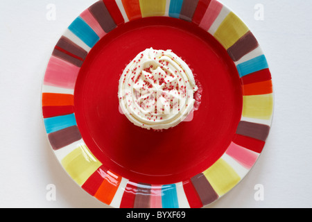 Looking down on Red velvet cupcake on brightly coloured red plate - from above - Stock Photo
