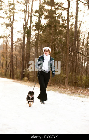 woman walking her dog in snow - Stock Photo